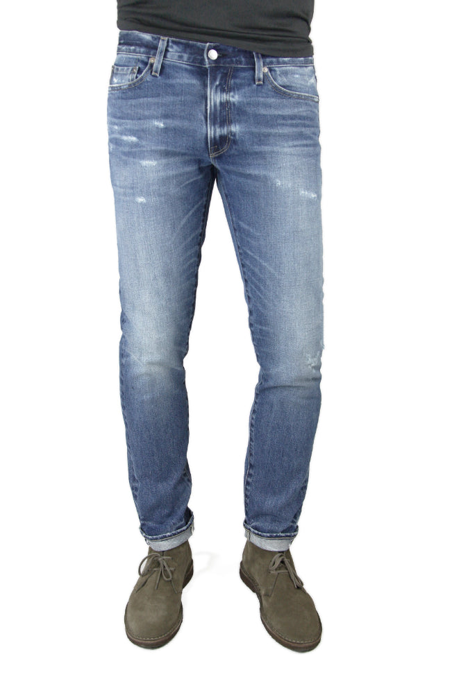 S.M.N Studio's Finn in Ace Men's Jeans. A tapered slim medium indigo wash stretch selvedge jean with light contrasting fades, whiskers, slight distressing and rips for a slight worn in look
