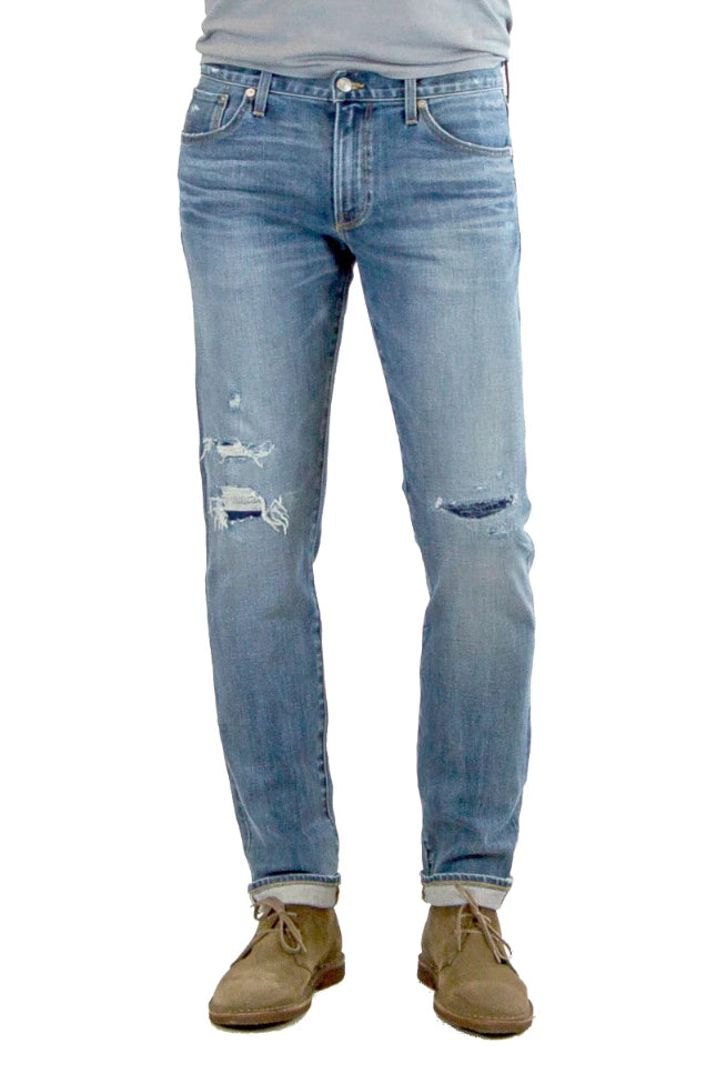 S.M.N Studio's Hunter in Baker Men's Jeans - Slim fit stretch selvedge denim in a medium wash denim finished with fades and distessing, repair detail on knees