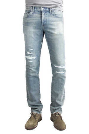 S.M.N Studio's Bond in Vernon Repair men's jeans. A slim straight jean made in a comfort stretch Japanese denim. Its light blue wash is contrasted with fading and repaired distressing around the knees with subtle rip details on the hems of the jeans.