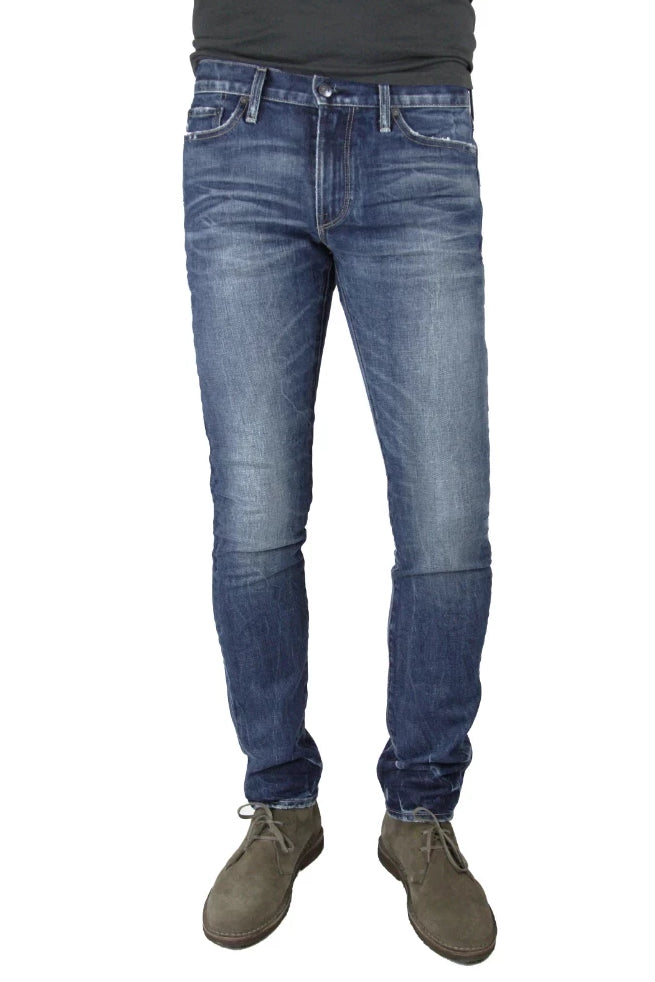 S.M.N Studio's Finn in Diver Men's Jeans. A tapered slim fit medium wash jean in comfort stretch premium Japanese denim. The wash is contrasted with 3D whiskers and fading for a naturally vintage look.