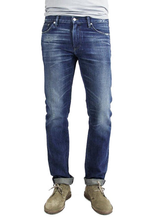 S.M.N Studio's Hunter in Rainer Men's Jeans - 100% Cotton Selvedge Slim fit jean made in a dark indigo wash contrasted with light fades, honeycombs, whiskers, and slight tear details