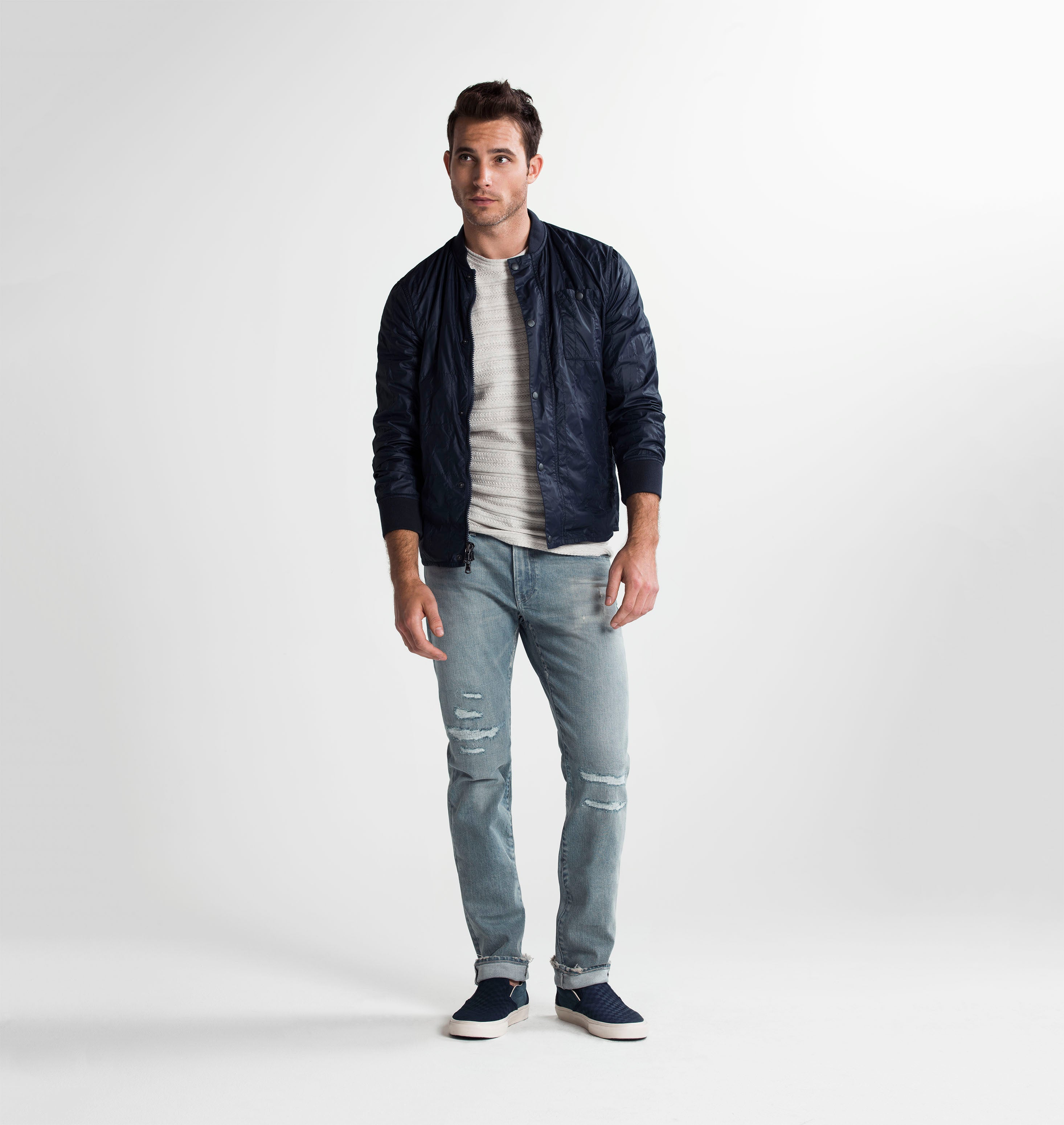 Brown haired athletic model standing and slightly bending his left knee while wearing a navy bomber jacket rolled up at his sleeves with a grey t shirt and S.M.N Studio's Bond in Vernon Repair jeans. The jeans are a slim straight jean in a light blue wash with repaired distressing at the knees and subtle rip details on the hems.