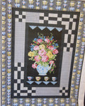 Quilt has flowers in a teapot panel with black and white borders.