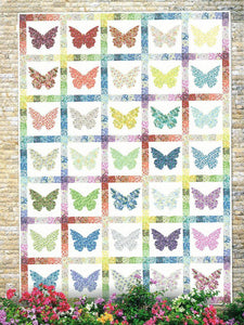 Small floral fabric are appliqued as butterflies on a white background.