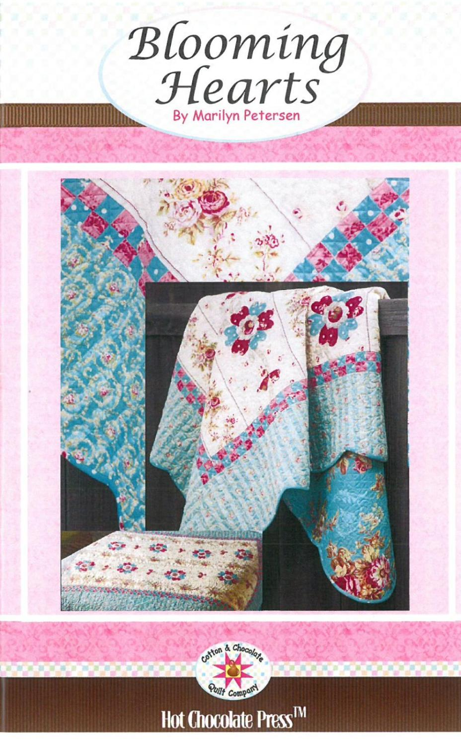 This quilt features printed and appliqued flowers with a checkerboard inner border and large blue and pink flowered outer border.