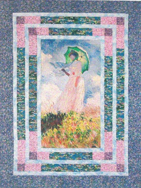 The center panel shows a woman holding a green umbrella on a hillside with a blue sky and clouds behind her.  Borders are done in pink, blue and purple floral fabric.