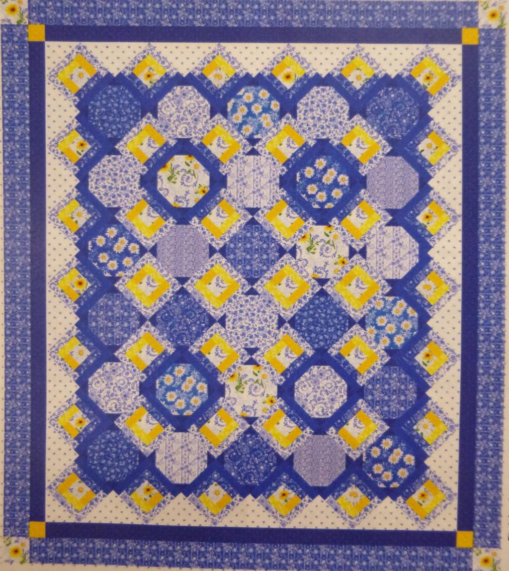Blue and yellow daisies and paisley prints as used in log cabin and snowball blocks in this quilt.
