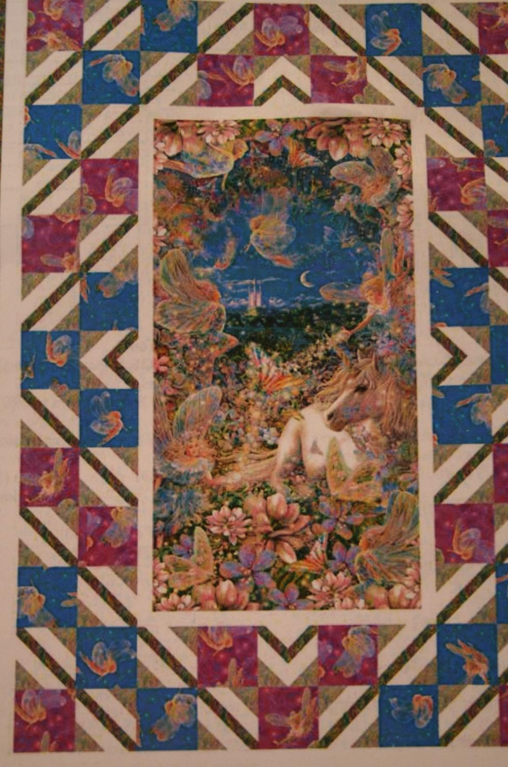 The center panel features fairies and a unicorn amongst flowers.  The border uses fairy fabric in blues and pinks.