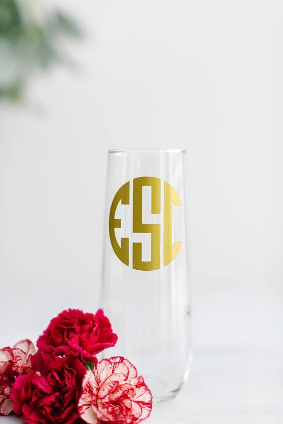 Close up of single bridal party glass monogram champagne flute next to beautiful pink flowers.