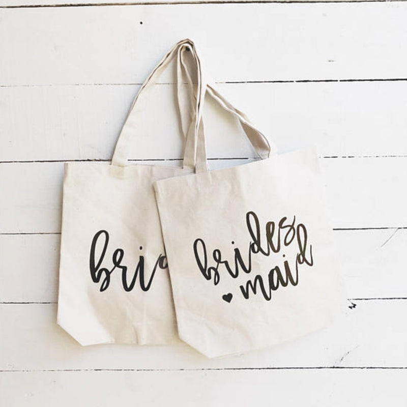 Sturdy medium size natural color bride and bridesmaid canvas tote bag for bridal party on white wooden background.