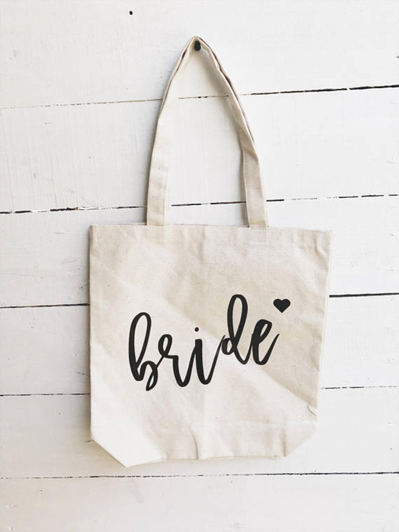 Sturdy natural color canvas tote for bridesmaid on white wooden backdrop.