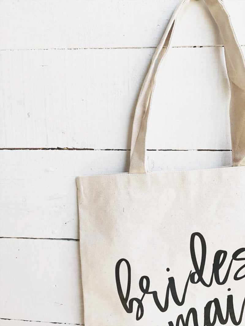 Close up of sturdy natural color canvas tote for bridesmaid on white wooden backdrop.
