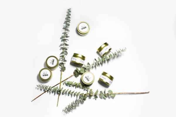 Natural hand poured soy lavender, earl grey, and lemongrass 4 oz candles spread out on white background with eucalyptus plants.