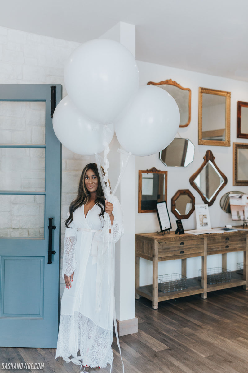 Bride holding large balloons in unique long white bridal robe by blue door in Hidden Pines Chapel in Flower Mound, Texas.