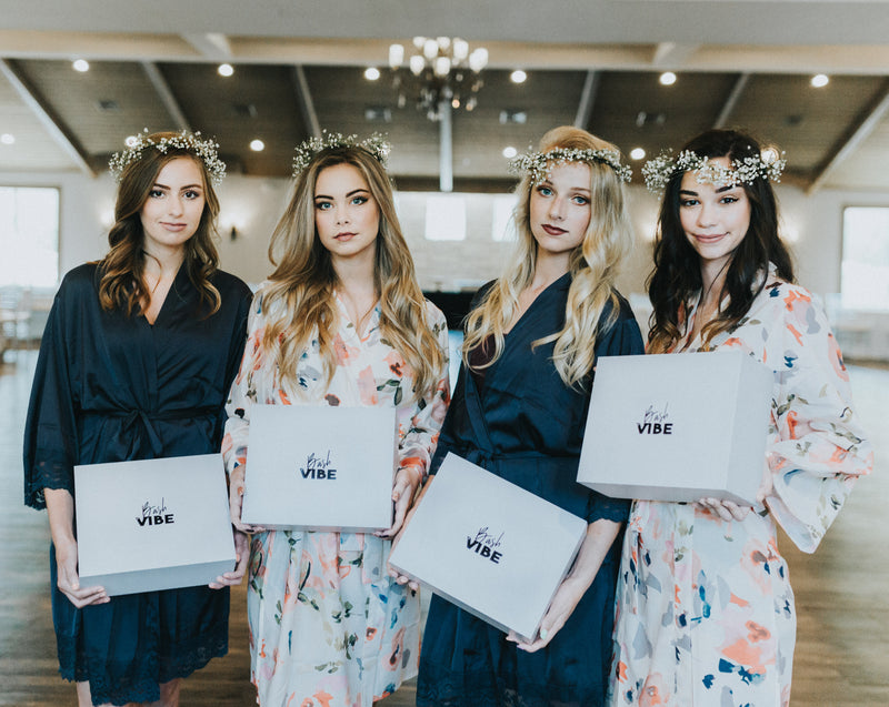 Bridal party holding their bridesmaid invitation boxes and wearing unique floral cream and blue bridesmaid robes.