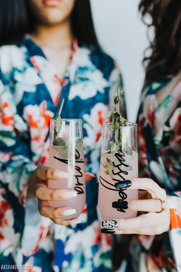 Woman holding personalized stemless champagne flutes with beautiful script font, wearing floral blue bridesmaid robes.