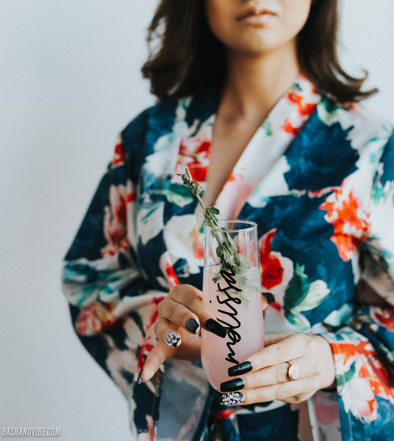 Bridesmaid holding personalized stemless champagne flutes with lemonade and mint, wearing beautiful bridal robe in the color blue with floral print.