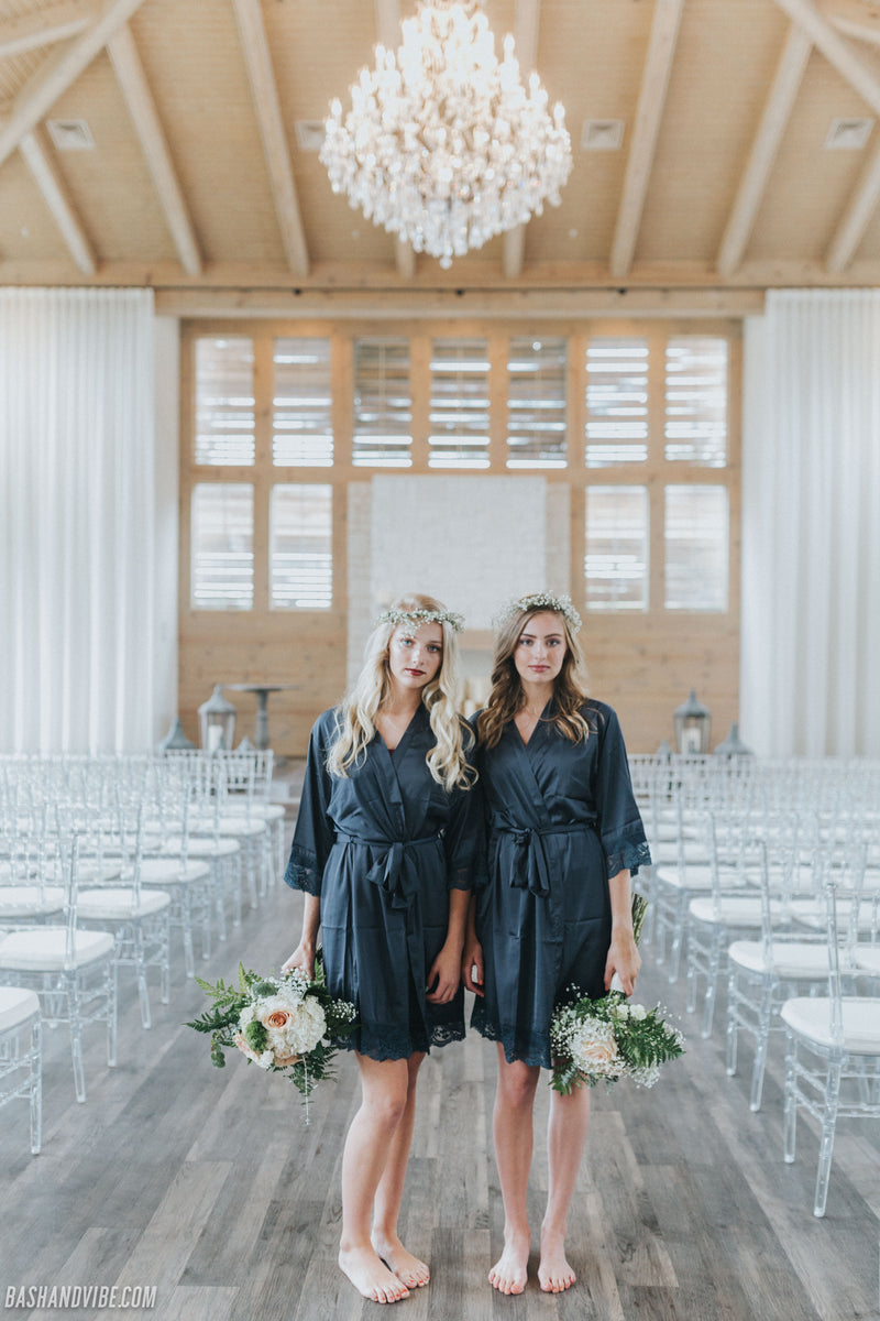 Bridesmaids on wedding day standing in ceremony aisle in Hidden Pines Chapel in Flower Mound, Texas, wearing beautiful blue lace robes.