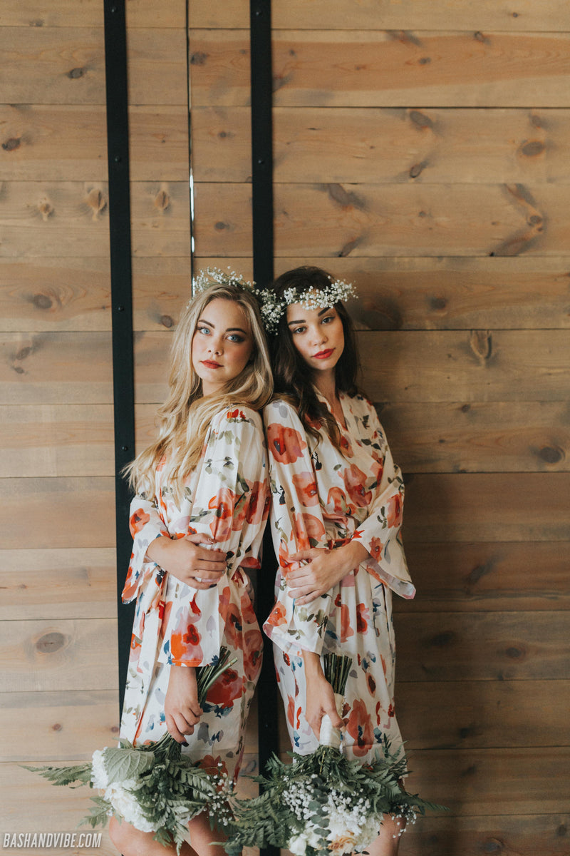 Bride and bridesmaid pose on wedding morning in cute floral bridesmaid robes, with floral crown and beautiful bouquets.