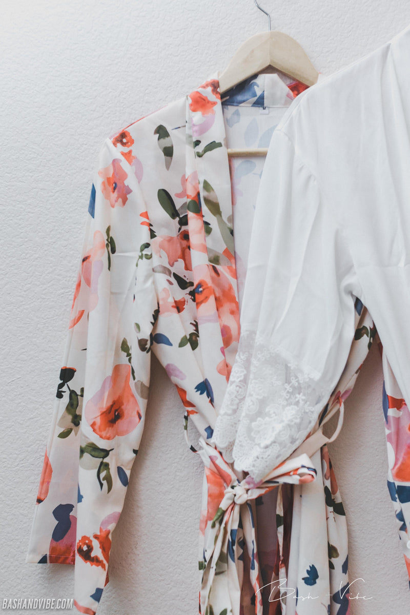 Close up of floral white bridesmaid robe and lace white robe hanging on wooden hanger.