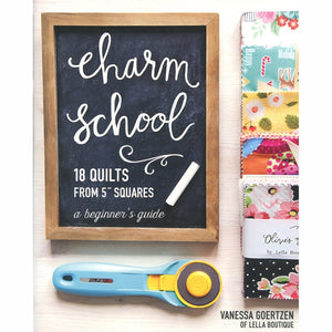 "front cover of the quilt book Charm School by Vanessa Goertzen of Lella boutique.  Show a Chalk board, rotary cutter and charm packs which are 5"" precut squares."