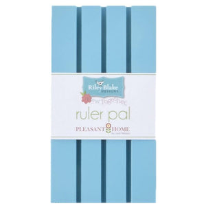 Ruler Pal is a piece of painted wood with shallow grooves to hold quilting rulers.  Aqua color designed by pleasant home for Riley Blake Designs.