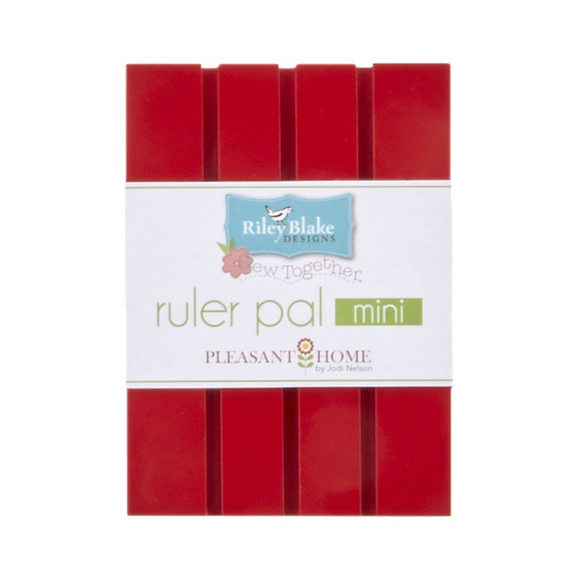 Ruler Pal Mini is a painted piece of wood with shallow grooves made for holding quilting rulers.  Red color. Designed by Pleasant Home for Riley Blake Designs.
