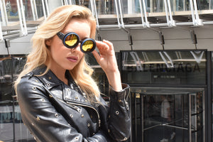 Blonde model wearing 1960s sunglasses by Nouvelle Chicane black lunette sunglasses & gold lenses in a leather jacket in Monaco Ville near Nouvelle Chicane at the Monaco grand prix