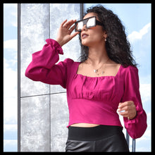 Load image into Gallery viewer, model in pink shirt wearing black sunglasses looking into the sunset