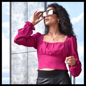 model in pink shirt wearing black sunglasses looking into the sunset