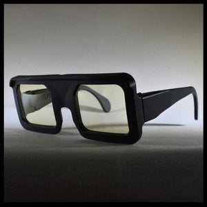black square sunglasses with yellow lenses on a table
