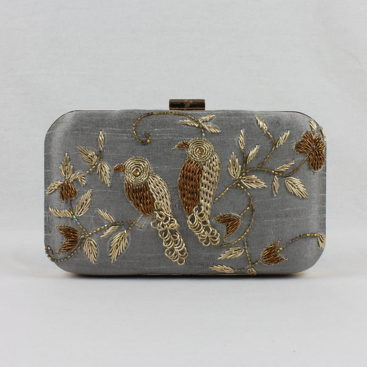 grey clutch bag with gold embroidered birds