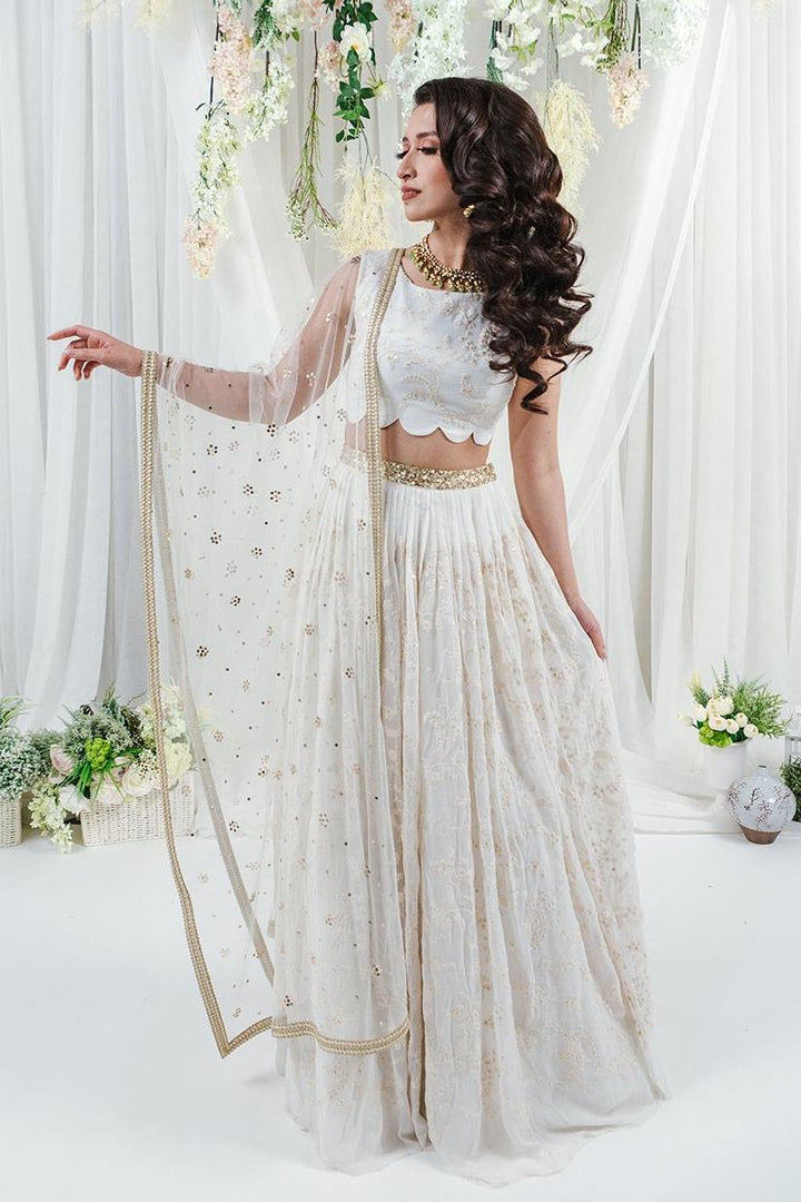 white lehenga with allover flower embroidery and gold waistband