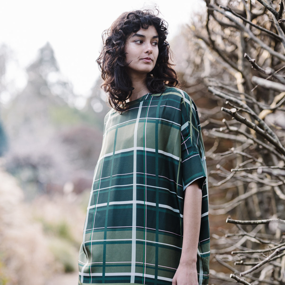 Woman wears green and navy checked Elin T-shirt dress against a leafy backdrop.