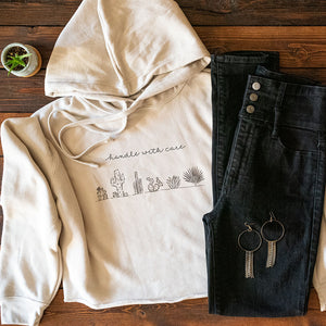 "Cropped Hoodie with cacti design and ""handle with care"" lettering on front. Comfy and stylish hoodie."