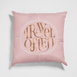 Throw pillow with Travel Often hand lettering in blush and rose gold