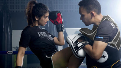 Kickboxing female knee kicking a male with mitts