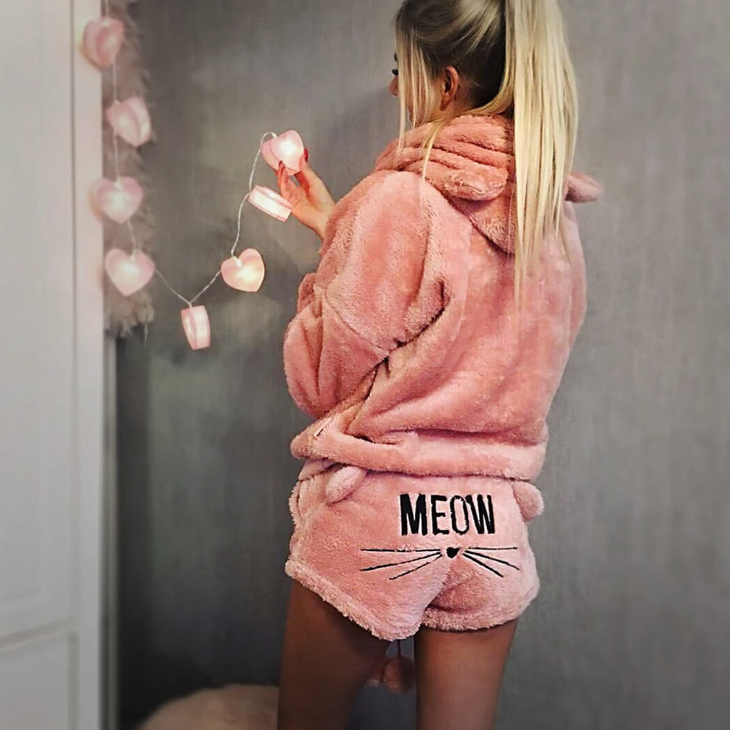 Woman wearing cute kitty pyjamas with cat ears and the word meow and cat whiskers sewn on
