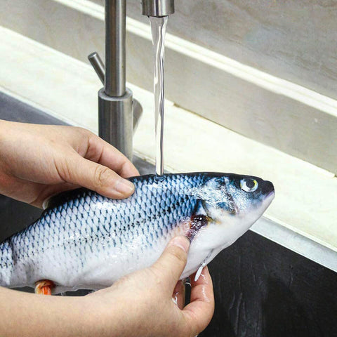 Clean your Cat Toy Fish: remove batteries and hand or machine wash! Image of plush fish being rinsed at sink