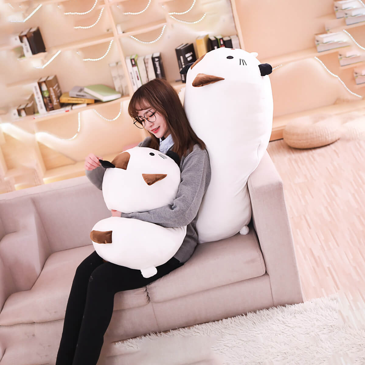 Cute Kawai Cat Pillow - Woman on couch with a medium and big sized soft cat pillow