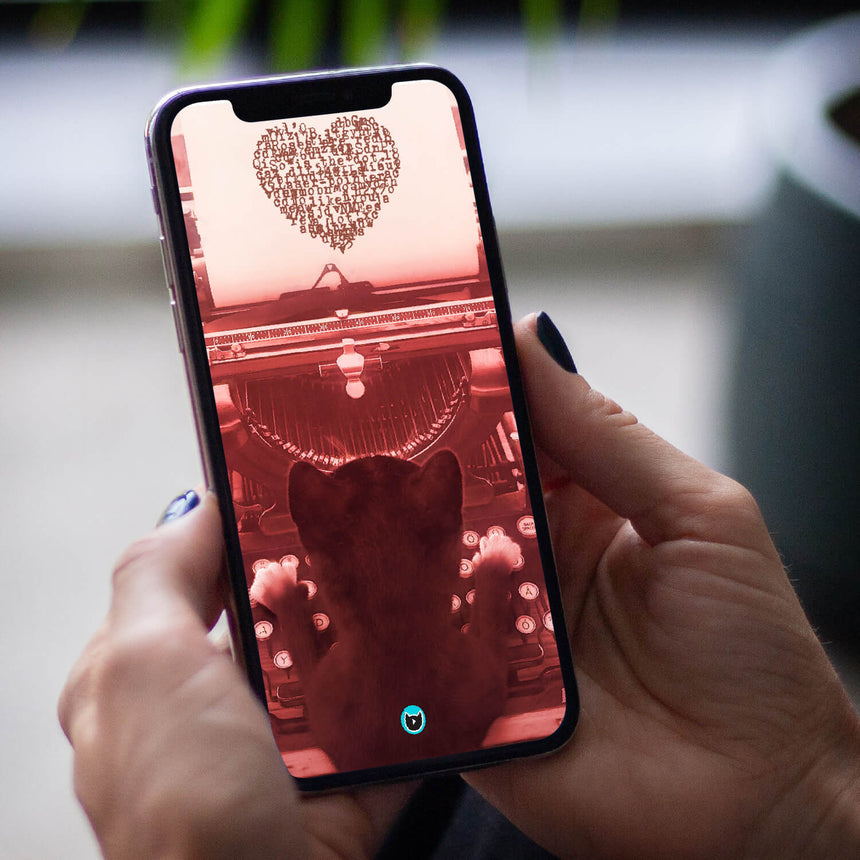 Felini the Kitty typing heart shaped letters wallpaper on a phone held by woman's hands