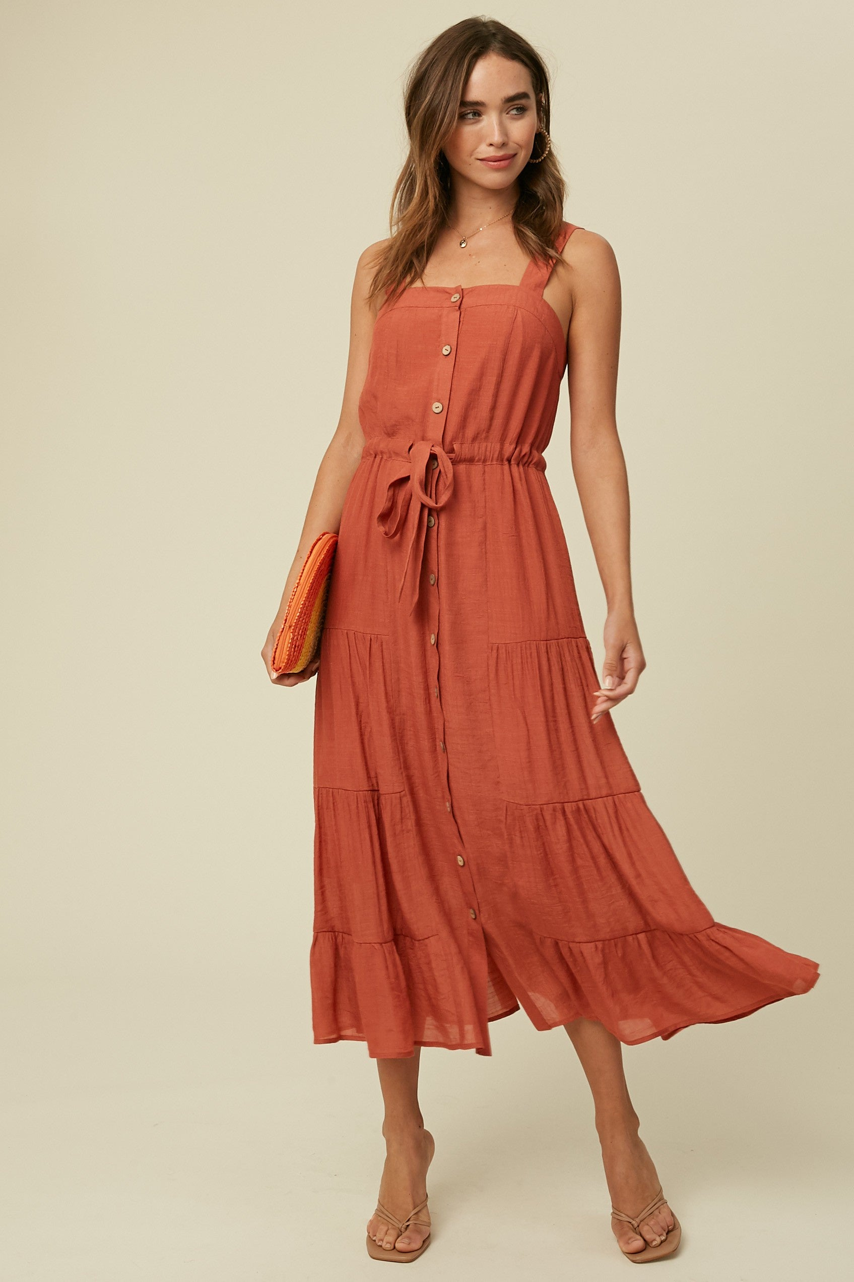 Model wearing a rust (red-orange) dress, features buttons all the way down the front, a drawstring at waist, sleeveless with a square neckline. Skirt has flowy tiers. Model paired with sandals and a bright woven clutch.