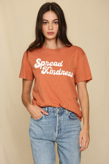 "model wearing retro font tee that reads ""sprad kindness"" in a muted red-orange color."