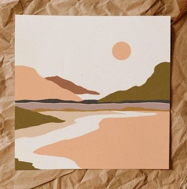 A painterly print of a day time desertscape, features mountains and a peach sun. In foreground is a white path leading back to the mountains. Colors are moss, peach, tan, mauve and clay.