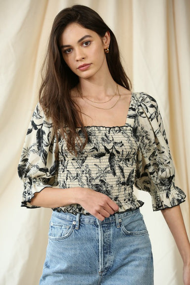 Model wears top with a fitted, smocked bodice, puff sleeve with elastic at ends, square neckline in a beautiful black and ivory floral print