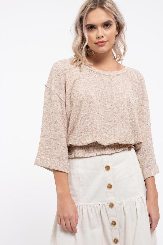 Blond Haired model wears the two tone top, shows wide sleeves, dropped shoulder, round neckline and smocked bottom hem giving the shirt more volume. Paired with an off white button front skirt.