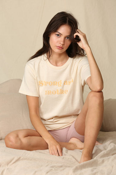 "Model wearing bone colored shirt with retro yellow font that reads ""strong as a mother"""