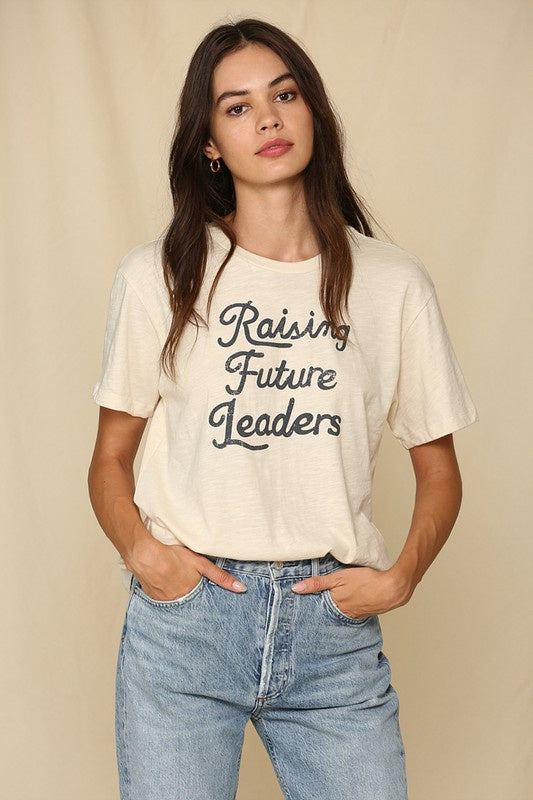"Model wearing bone colored shirt with retro dark gray font that reads ""Raising Future Leaders"""