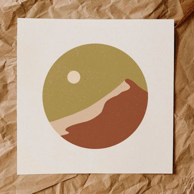 Minimalist print has no defined lines, features a mustard color speckled sky with cream color moon to the left, warm brown mountain with a peach side. Design is a circle shape with white background.