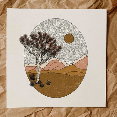 Art print featuring an oval shape with a Joshua Tree and shrubs in the front and mountains in tan and terracotta shades in the back. Sky has hashmark design and godl sun.